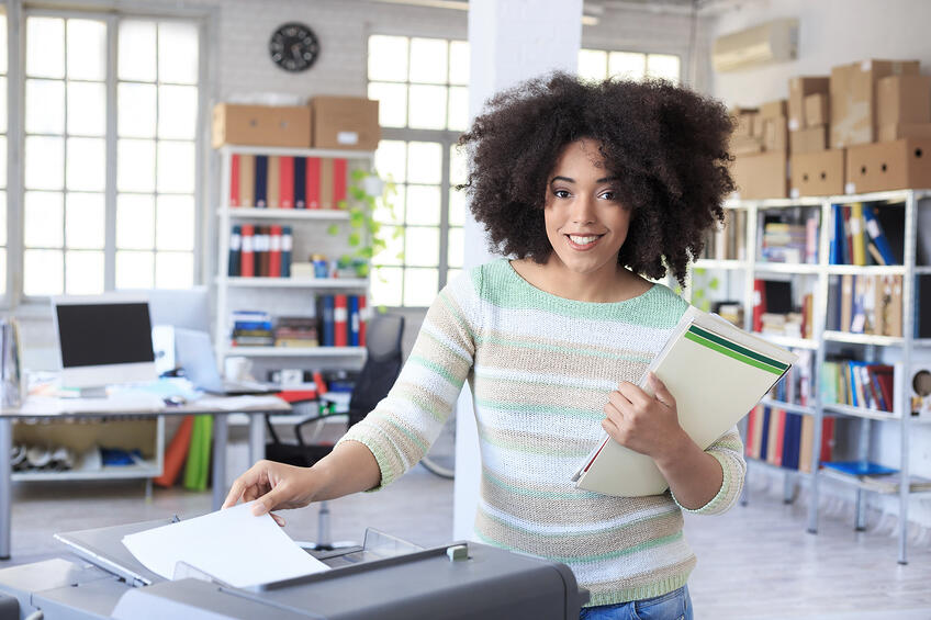 Smiling assistant using copy machine at work